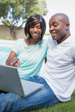 Happy couple sitting in garden using laptop together. On a sunny day Stock Photo