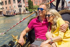 Happy couple sitting in gondola on their vacation Stock Photography