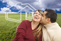 Happy Couple Sitting in Grass Field with Ghosted House Behind Royalty Free Stock Photography