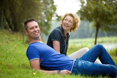 Happy couple sitting on grass outdoors Royalty Free Stock Photography