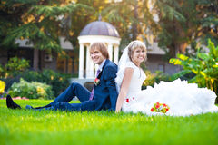 Happy couple are sitting on the green grass Stock Photo