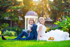 Happy couple are sitting on the green grass Royalty Free Stock Image