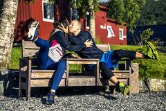 Happy couple sitting and kissing on the bench, Norway Stock Photo