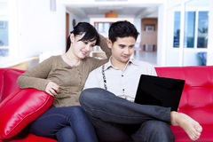 Happy couple sitting with laptop at home Stock Image