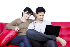 Happy couple sitting with laptop - isolated Royalty Free Stock Photos