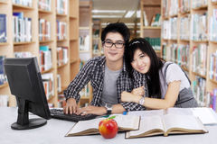 Happy couple sitting in library Royalty Free Stock Image