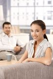 Happy couple sitting in living room at home Stock Photos