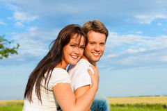 Happy couple sitting on a meadow Royalty Free Stock Photography