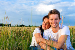 Happy couple sitting on a meadow or grainfield Stock Image