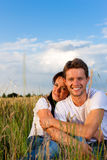 Happy couple sitting on a meadow or grainfield Stock Photography