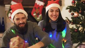 Happy couple sitting near christmas year tree, waving sparklers in hands. Woman gives present to man, they kissing. Man and woman in home clothes sitting near stock video