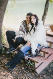 Happy couple sitting near lake in an autumn forest Royalty Free Stock Images