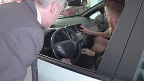 Happy couple sitting in new auto, examining it, vehicle dealer showing car to buyers. stock video footage