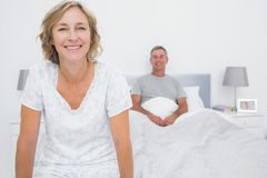 Happy couple sitting on opposite ends of bed. Smiling at camera in bedroom at home stock photos