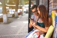 Happy couple sitting outside in a cafe and watch phone Royalty Free Stock Photo