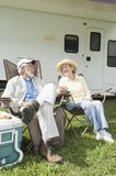 Happy Couple Sitting Outside RV Home. Full length of happy senior couple sitting on folding chairs outside RV home Royalty Free Stock Photography