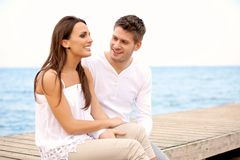 Happy Couple Sitting on a Pier Royalty Free Stock Photos