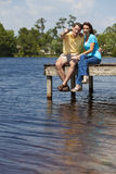 Happy Couple Sitting On A Pier By Lake Stock Photography