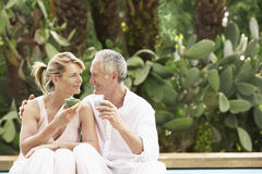 Happy Couple Sitting By Pool Drinking Tea Royalty Free Stock Images