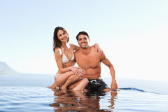 Happy couple sitting on pool edge Stock Images