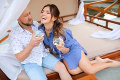 Happy couple sitting on resort, drinking wine near candles. stock photos