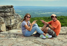 Happy couple sitting on the rock at Minnewaska State Park Stock Images
