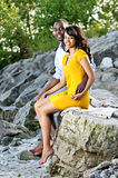 Happy couple sitting at rocky shore Stock Image