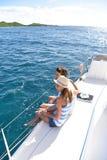 Happy couple sitting on sailing boat cruising on caribbean islands Royalty Free Stock Photos