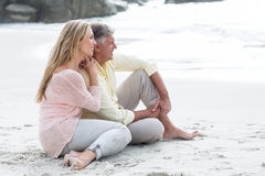 Happy couple sitting on the sand Royalty Free Stock Photo