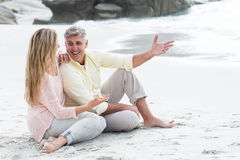 Happy couple sitting on the sand Stock Photography