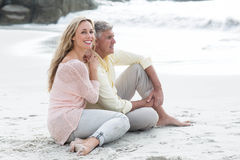 Happy couple sitting on the sand Stock Image