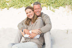 Happy couple sitting on the sand Stock Image