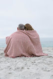 Happy couple sitting on the sand with blanket around them Stock Photos