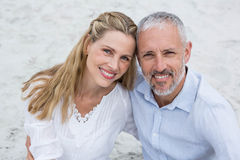 Happy couple sitting on the sand and looking at the camera Royalty Free Stock Photo