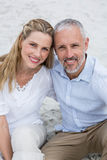 Happy couple sitting on the sand and looking at the camera Royalty Free Stock Image