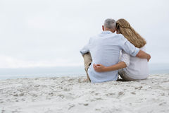 Happy couple sitting on the sand and looking at the sea Stock Photo