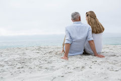Happy couple sitting on the sand and looking at the sea Royalty Free Stock Images