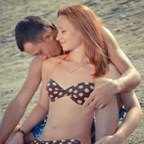 Happy couple sitting on sandy beach embracing & kissing Stock Image
