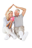 Happy couple sitting and sheltering piggy bank Stock Photography