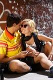 Happy couple sitting on sidewalk Stock Image