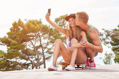 Happy couple with sitting on skateboard and taking a selfie Stock Photo