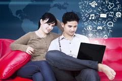 Happy couple sitting on sofa with flying alphabet Stock Photo