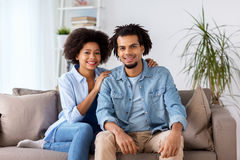 Happy couple sitting on sofa at home Stock Photography