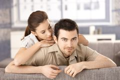 Happy couple sitting on sofa hugging each other Royalty Free Stock Image