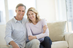 Happy Couple Sitting On Sofa In Living Room Royalty Free Stock Photography