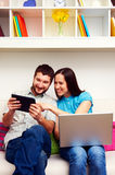 Happy couple sitting on sofa Stock Photography
