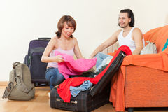 Happy couple sitting  on sofa and packing suitcase Stock Photo