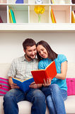 Couple sitting on sofa and reading the book Stock Photo