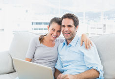 Happy couple sitting on the sofa using laptop together Stock Photo
