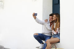 Happy couple sitting on stairs taking a selfie, Ibiza, Spain Royalty Free Stock Image